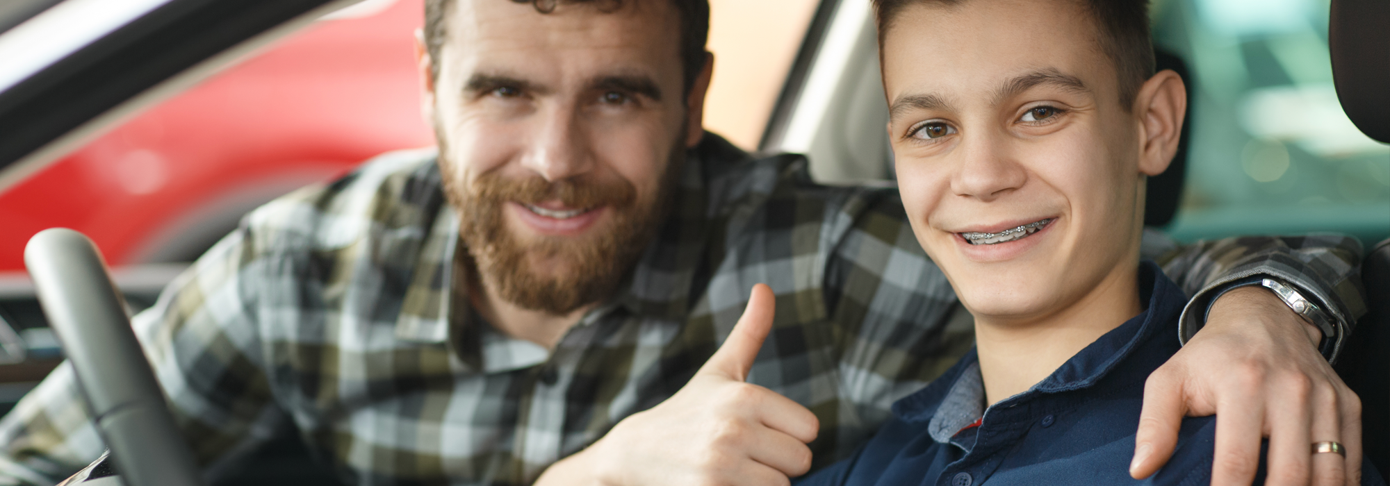 Teen giving thumbs up in drivers seat and dad in car.