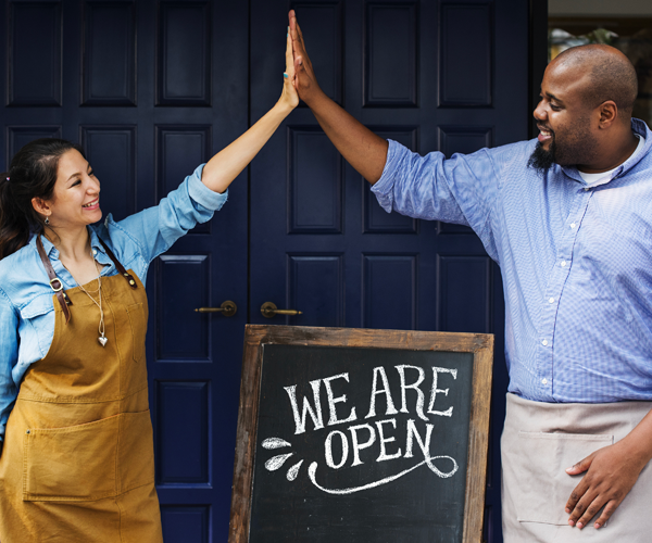 Man and woman high-fiving business open