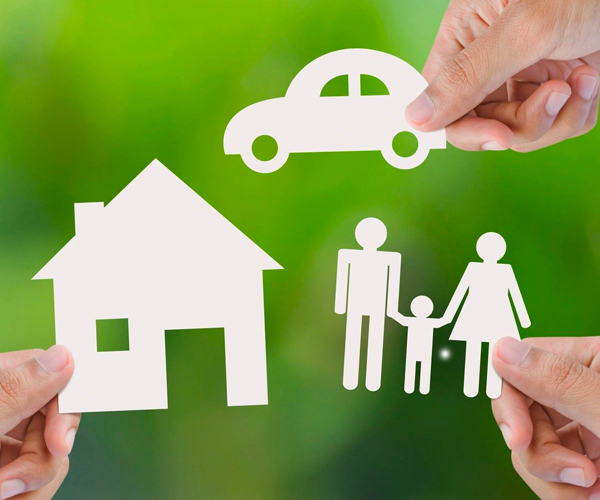 House, family and car paper cut outs on natural green background
